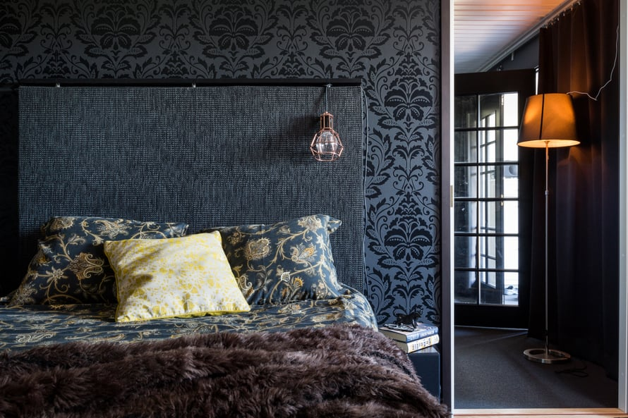 Musta sängynpääty sulautuu väritykselläään seinään. Tummat sävyt rauhoittavat. Kuva Tiiu Kaitalo
