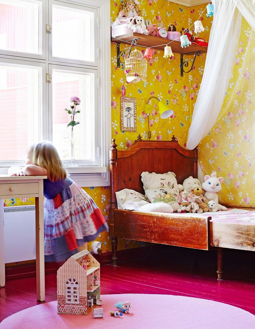 Lapsen huoneen tapetin sävyt sopivat upeasti fuksianpunaiseen lattiaan.