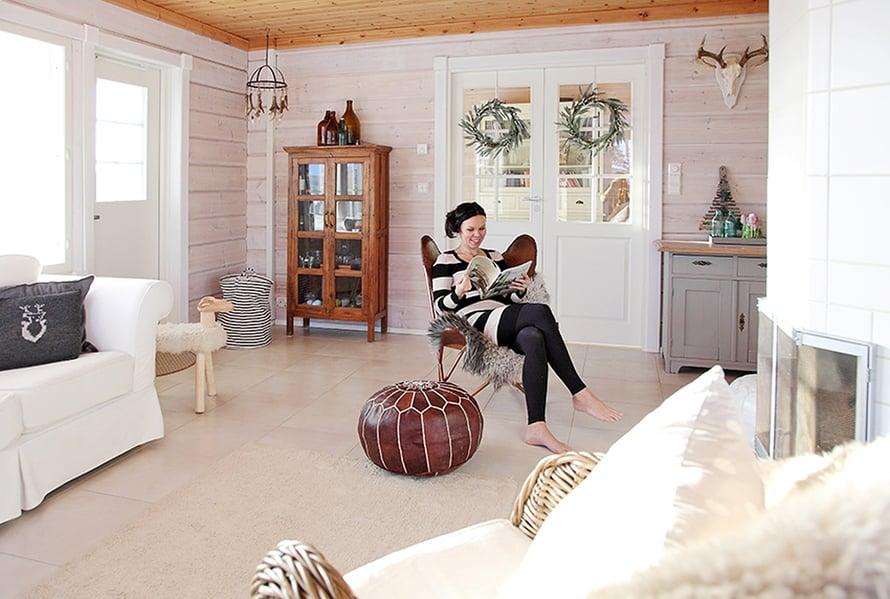 Olohuoneen lepakkotuoli on Tarjan lempipaikka. Hän maalasi edellisen talon kellarista löytyneen kirkkaanpunaisen patakaapin uuden kodin sävyihin sopivaksi. Paikallinen metsästäjä lahjoitti peuransarvet.