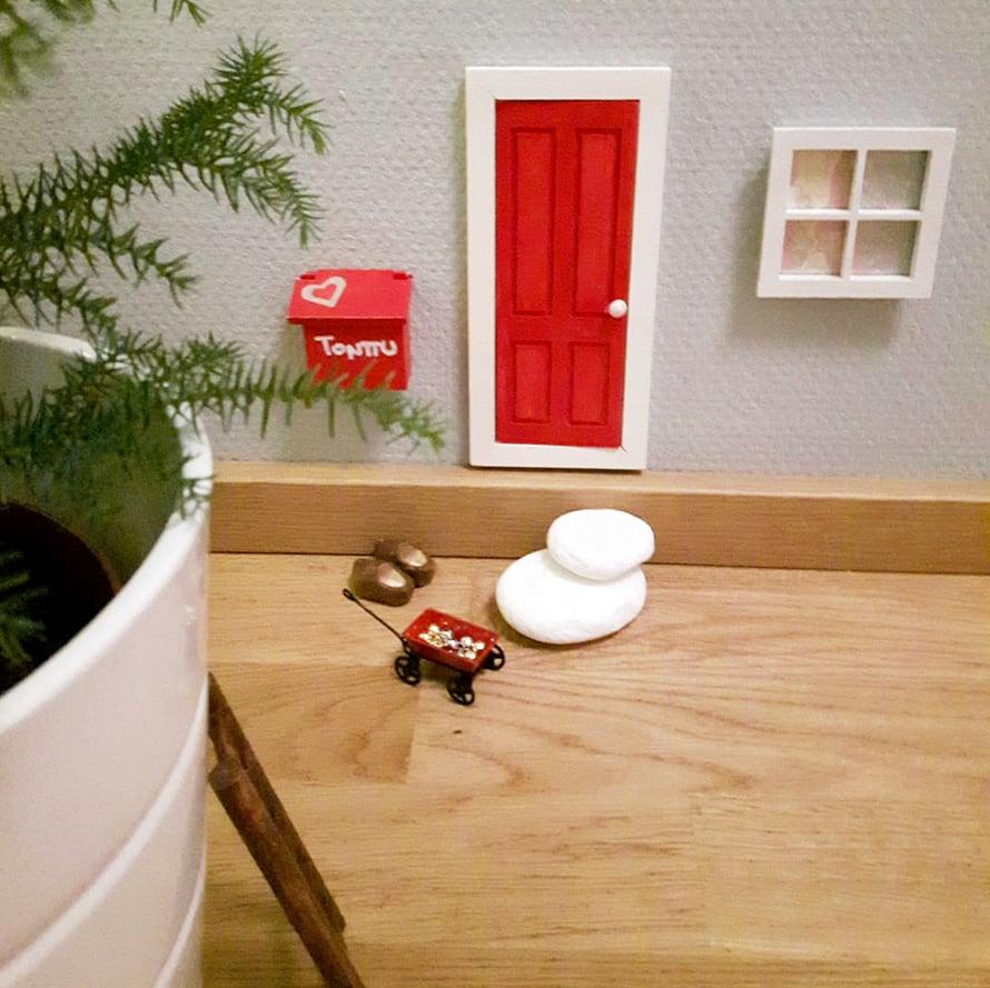 """""""Ovi, postilaatikko, tontun kengät ja tikkaat ovat askartelukaupasta, mutta maalasin ne itse. Ikkuna on tilattu Wish-nettikaupasta- Liimasin sinne joulukortista kuvan. Tonttu rakentaa kun kiireiltään kerkeää. Ikkuna ilmestyi viime yönä. Tonttu toimii myös joulkalenterin täyttäjänä ja koristeli jo huonekuustakin."""" Hanne Helasuo"""