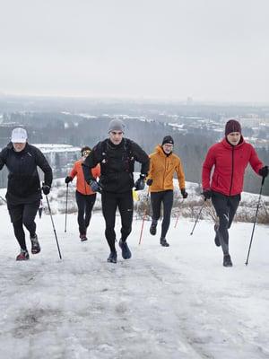 """Malminkartanon täyttömäki on lumesta liukas, mutta Nyyti (vas.), Tomas, Niko ja Janne eivät vaihda kävelyksi. """"Juoksu tukee addiktien  toipumista, kunhan treenaus ei mene överiksi. Tärkein tehtäväni on muistutella lepopäivistä"""", valmentaja Juhani (oik.) sanoo."""