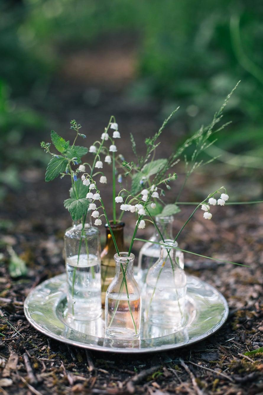 Vanha lasipullo tai maitokannu ovat maljakoista parhaita. Halutessaan asetelman voi rakentaa hopeanväriselle lautaselle.
