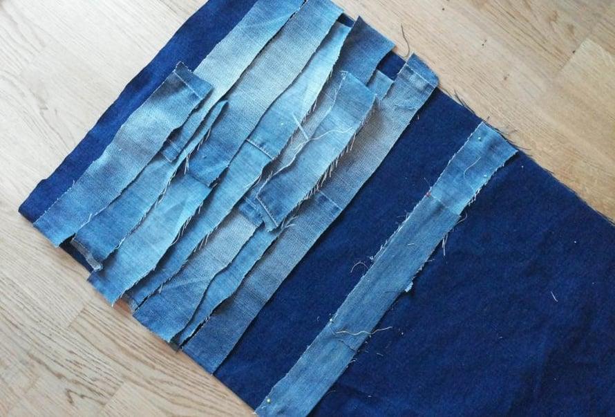 Tyynyä varten leikkaa farkuista 3–4 cm:ä leveitä suikaleita. Ne voivat olla eri pituisia. Leikkaa tummansinisestä farkkukankaasta 44 cm leveä ja 84 cm pitkä pala, johon suikaleet kiinnitetään.