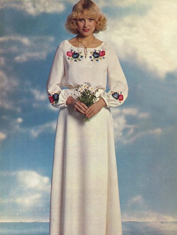 Hele Patjaksen vuonna 1975 suunnittelema yhdistelmäasu sopii käytännölliselle morsiamelle. Asuun kuuluu ruusuilla ja kaunokeilla kirjottu pusero ja kietaisuhame.