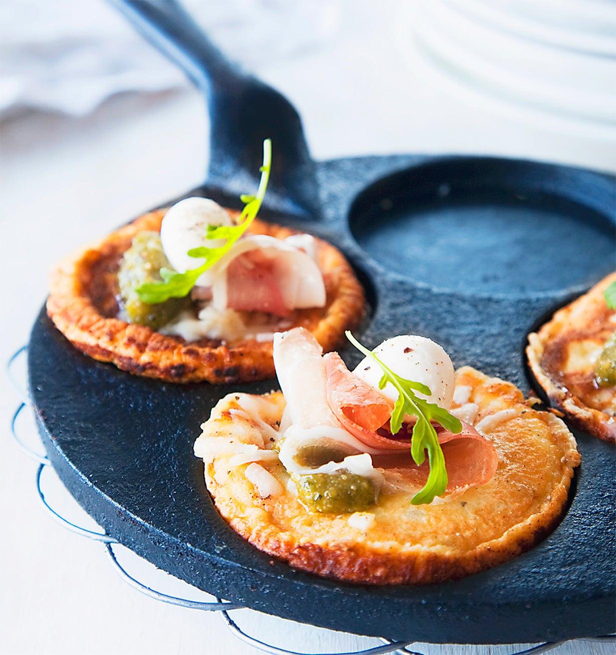 Pienet pannukakut paistetaan lettupannulla. Niiden juju on suolainen parmankinkku-pesto-mozzarellatäyte.