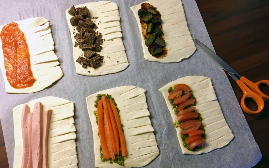 Ylärivissä ruusunmarjasosetta, tummaa leivontasuklaata ja salmiakkitoffeeta. Alarivissä nakkiviipaleita, porkkanasuikaleita ja tomaattiviipaleita.