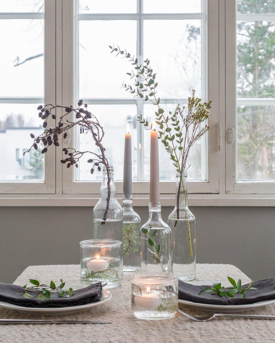 Kata jouluisen pöydän koristeeksi ilmava asetelma oksia ja kukkavarsia. Lisää pulloihin ja purkkeihin vettä ja työnnä koristeeksi eukalyptusta, vahakukkaa, havuja ja lepän urpujen koristelema oksa.
