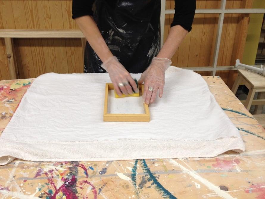 Kumoa paperimassa viirasta nopealla liikkeellä alustalle. Kuivaa sienellä verkon päältä, niin viira irtoaa helpommin. Irrota viira varovasti. Paperimassa jää lakanaan kiinni.