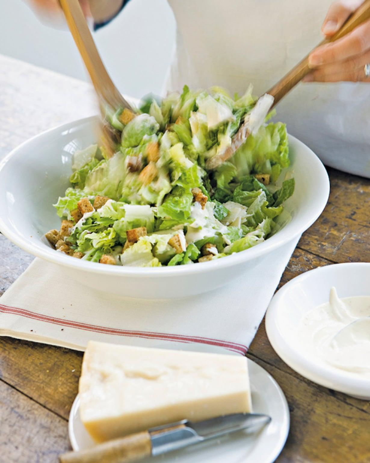 Vuole salaatin päälle parmesaanilastuja. Ripottele pinnalle jäähtyneet leipäkuutiot. Kaada 2/3 kastikkeesta salaatille ja sekoita ilmavasti nostellen.