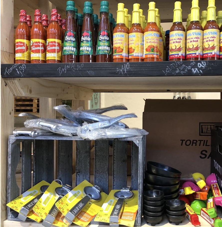 Tortillaprässi ja limemehun puristin ovat tärkeitä vempeleitä meksikolaisessa keittiössä. Kuvan chilikastikerivistö on vain kuudesosa kaupan koko valikoimasta ja kaikkia laatuja pääsee maistelemaan kaupassa.