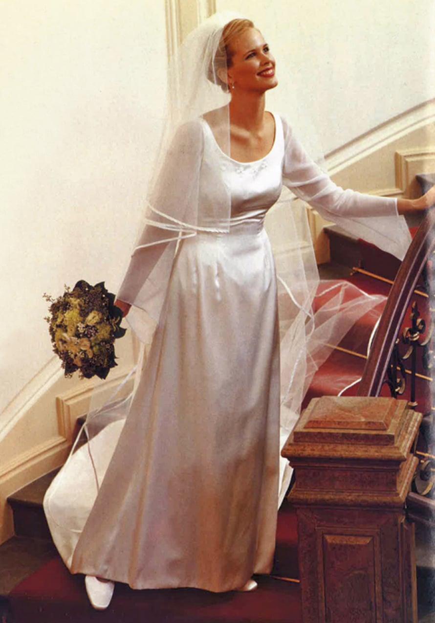 Heli Kujala-Bradley suunnitteli linjakkaan satiinipuvun vuonna 2001. Kellotetut sifonkihihat ja tyllihuntu kruunaavat komeuden.