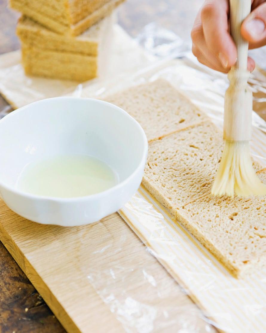 Vuoraa leikkuulauta elintarvikekelmulla. Asettele sille kolme leipäviipaletta rinnan ja kostuta ne. Höttöinen leipä tarvitsee vähemmän kostutusta kuin tiivis.