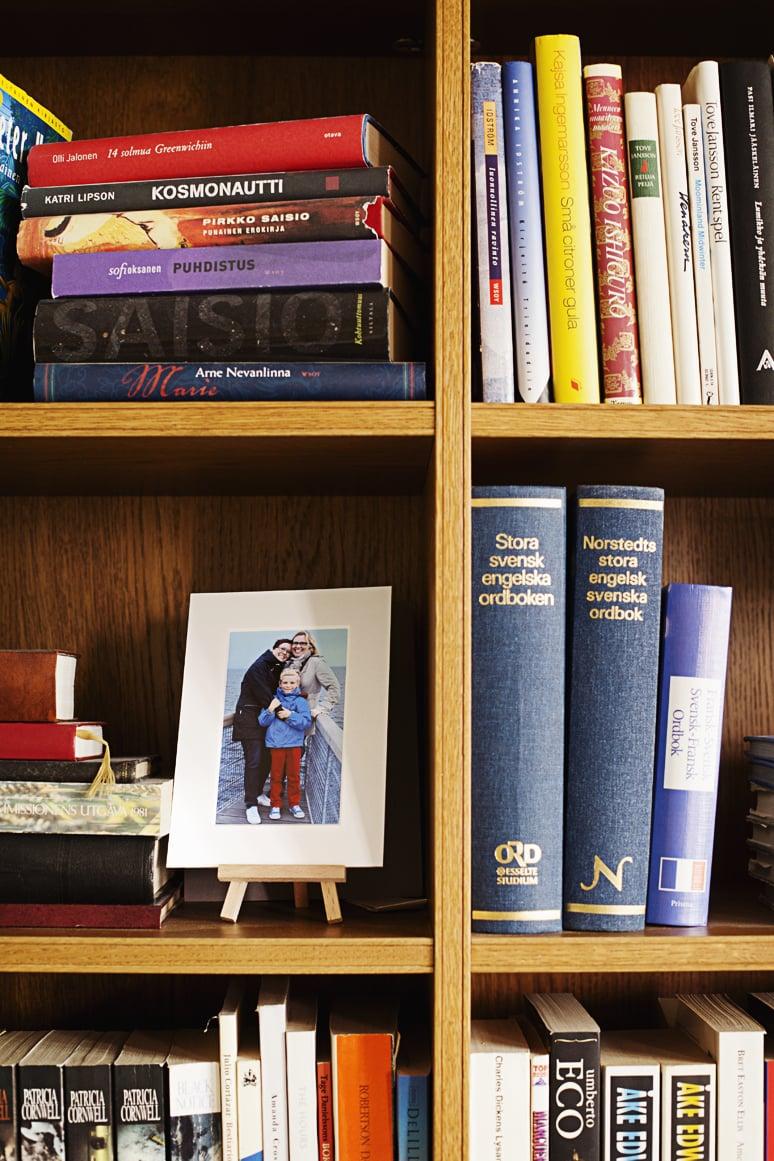 Kirjahyllyssä ovat perhekuva, romaanit ja sanakirjat.