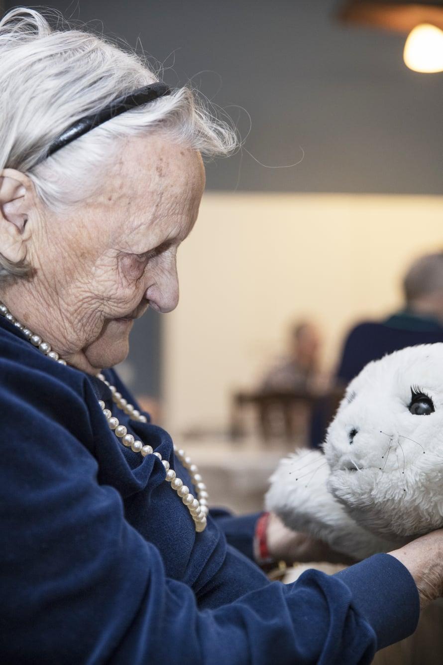 """Hilkka, 96, on hoitokoti Iltatähden vanhin asukas ja tietää hyvin, ettei Paro ole elävä olento. Silti sitä on mukavaa silitellä. """"Ihan kuin se nauttisi siitä, että rapsutellaan."""""""