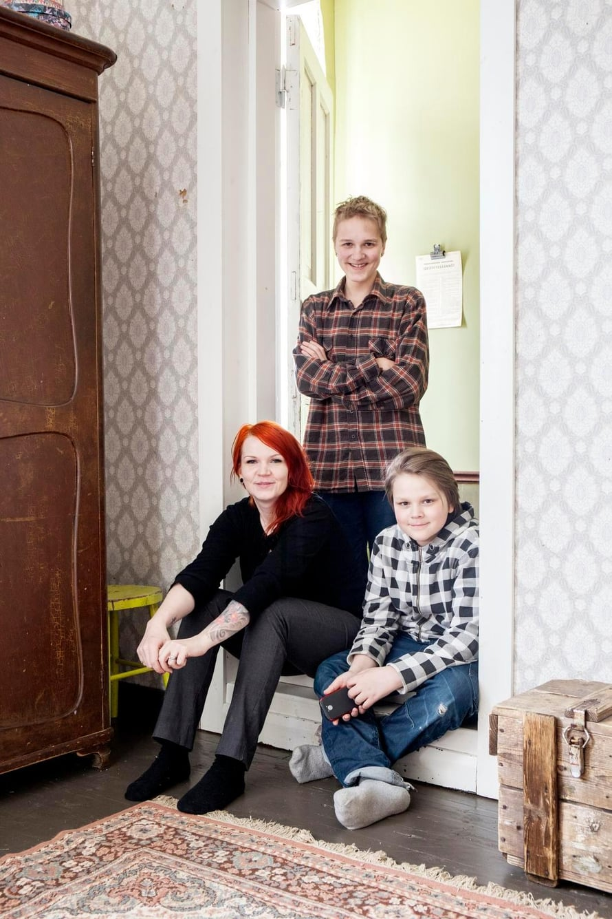 Jenni, Micael ja Cristofer poseeraavat vanhempien makuuhuoneen ovella. Huoneen kaunista, vanhaa tapettia ei tee mieli vaihtaa.