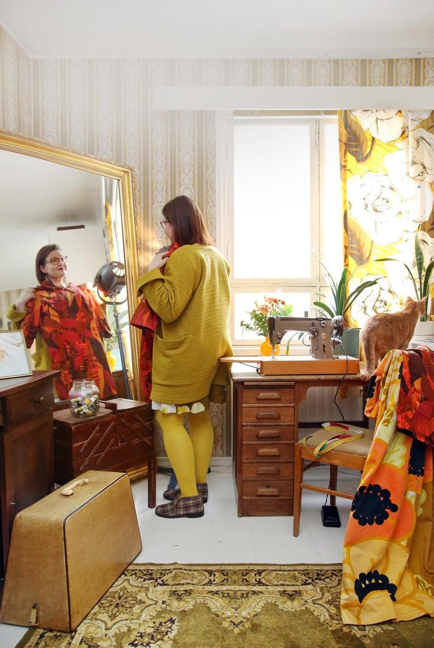 Peilistä näkyvä mekko on Marjatan tyttären Katariina Metsovaaran suunnittelemaa Tapiola-kangasta. Verhot ovat Valkeat Ruusut -kuosia ja tuolilla on Anemona-kangasta.