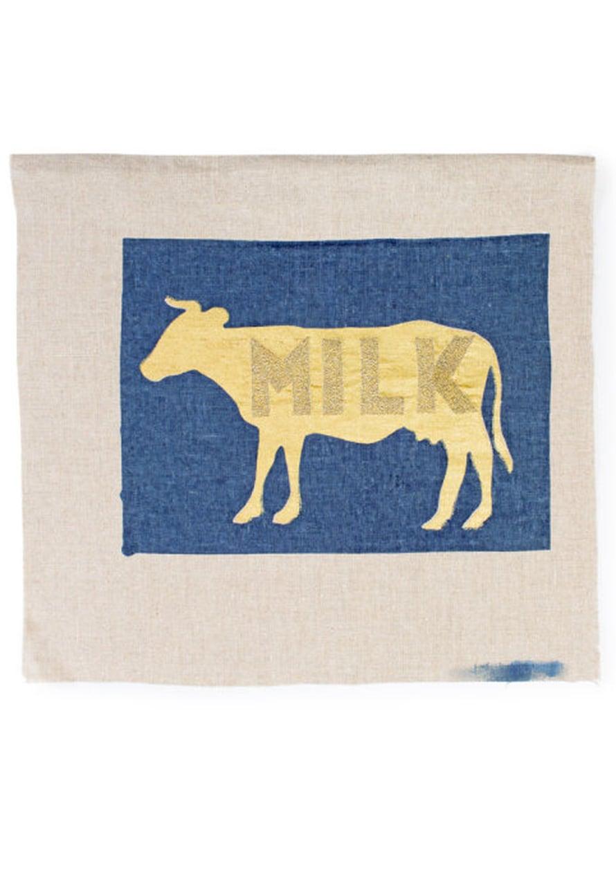 Tupu aikoo tehdä sarjan eläintyynyjä. Hän painoi ensin kullanvärisen lehmän pellavalle, sitten sinisen taustan ja kirjoi lopuksi tekstin ompelukoneella.