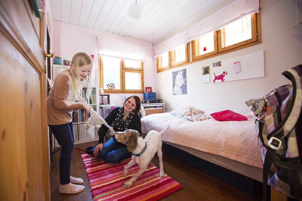 Maria Juntunen muutti tähän huoneeseen 30 vuotta sitten. Nyt siinä asuu hänen esikoisensa Miisa. Sulo-koira viihtyy siellä missä Miisakin.
