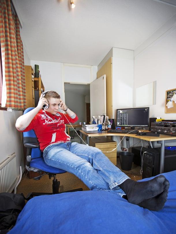 """Tatu Jauhiainen, 22, muutti Helsinkiin opiskelija-asuntoon Oulusta. Luurit päässä musiikki ei häiritse kämppistä. """"Sanon huonetta sekä kämpäksi että kodiksi. Kämppä on oululaiselle uusi termi."""""""