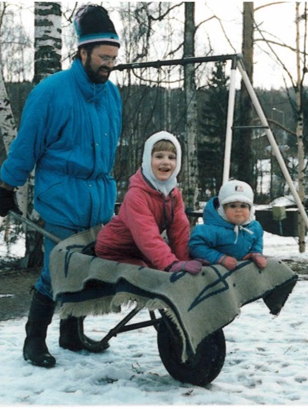 """Kuvassa Nelli Vuoristo isosiskonsa Jennin ja Vesa-isän kanssa Jyväskylän Palokassa 1980-luvun lopulla. Nelli kertoo: """"Kun olin neljän, lakkasimme mökillä isosiskonikanssa kynsiämme. Erään kerran isäni heitti vitsillä, että lakatkaapa minunkin varpaankynteni. Kun olin lakannut isän kynnet pinkillä lakalla, isä alkoi hassutella ja lakkasi toisella värillä ukkovarpailleen silmät ja suun."""""""