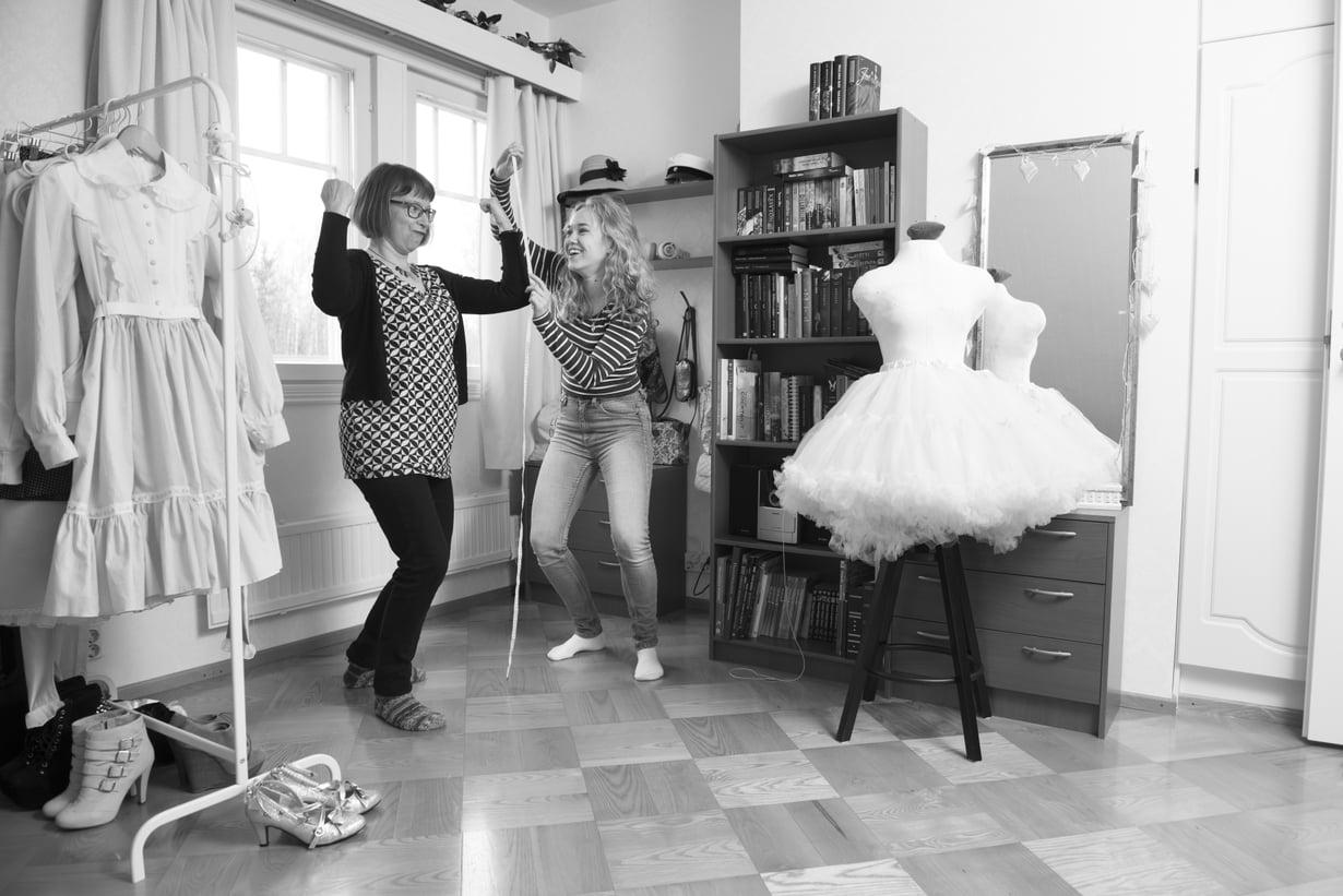 Lenita ottaa mittaa Pauliina-äidistä. Lenita pitää japanilaisesta Lolita-tyylistä ja harrastaa siihen kuuluvien mekkojen ompelemista.