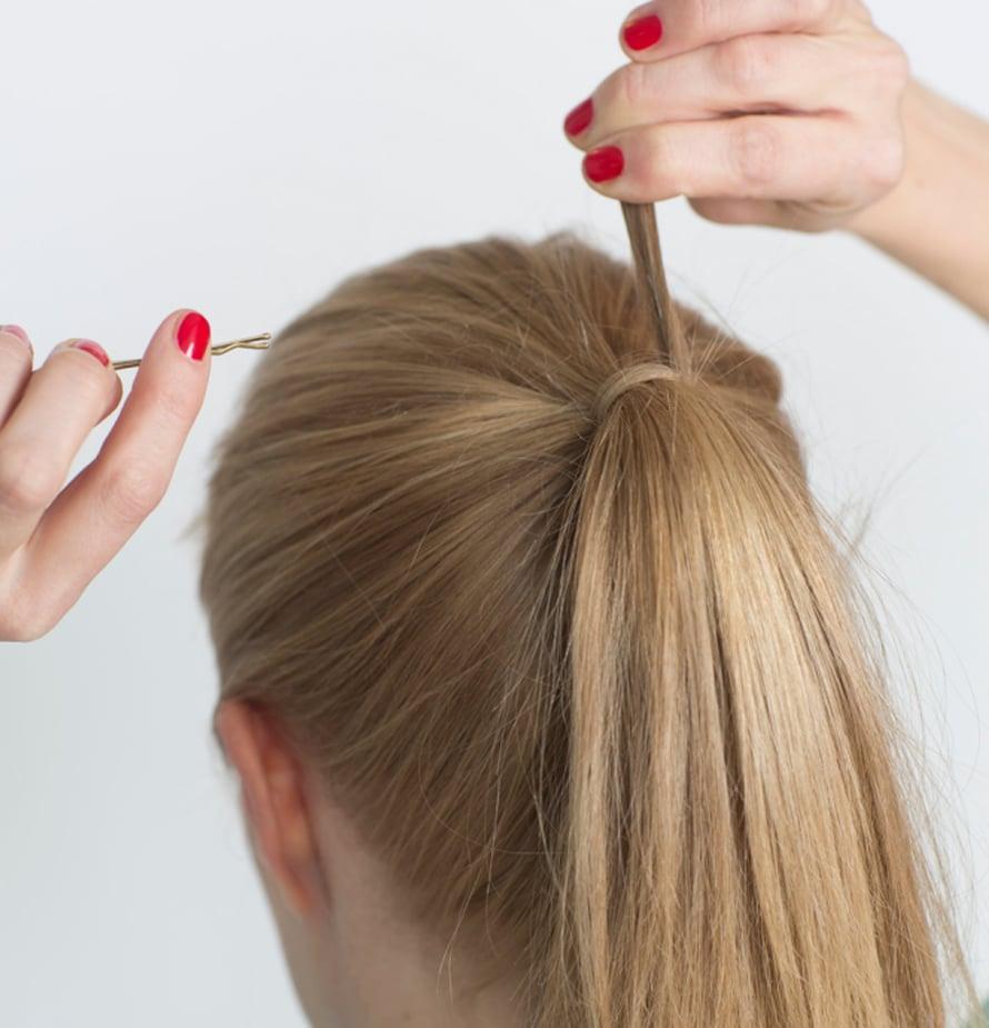 Kiinnitä kaksi pinniä hiuslenkkiin. Aseta toinen pinneistä ponnarin keskikohtaan pystysuunnassa. Pyöräytä hiuslenkki ponnarin ympärille. Aseta toinen pinni pystysuunnassa edellisen viereen. Näin ponnari pysyy koko päivän tukevasti paikoillaan. Piilota hiuslenkki pyöräyttämällä sen ympärille kapea hiusosio. Suihkauta ponnariin lopuksi hiuskiinnettä.