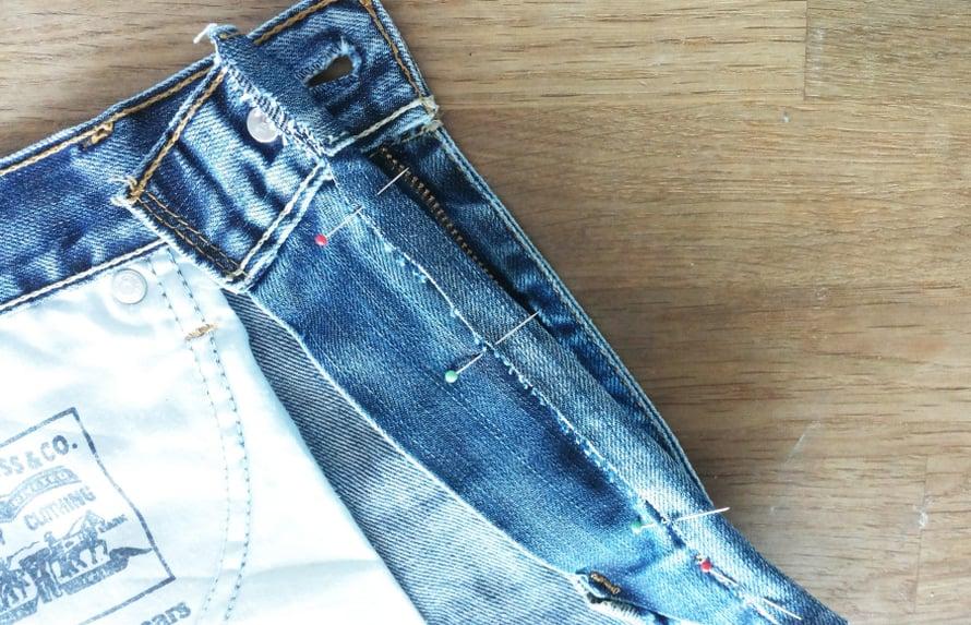 Saat tuolitaskun farkkujen oikeasta etutaskusta. Leikkaa farkut sivusaumaa pitkin auki. Leikkaa kangas vetoketjun vierestä auki niin, että ketjun viereen jää noin 1 cm:n käännösvara. Katkaise kangas muutama sentti vetoketjun alapuolelta molemmista reunoista. Voit muotoilla taskun alareunan halutessasi pyöreäksi tai v-malliseksi. Taita käännösvara nuppineuloilla nurjalle puolelle ja ompele se kiinni käsin.