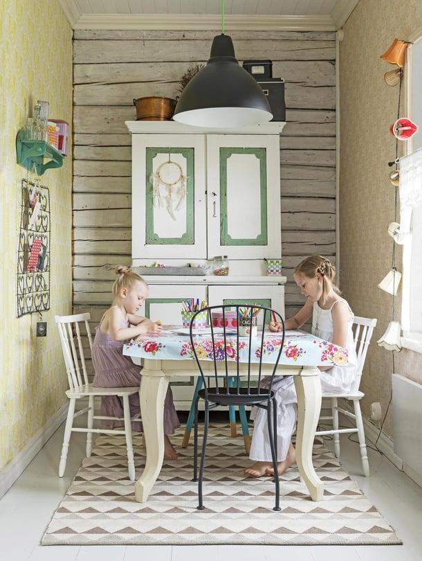 Huldan ja Thelman piirtelyhetki autiotalosta pelastetun pöydän ääressä. Kaappi, jossa säilytetään askartelutarvikkeita, on kirpputorilöytö.