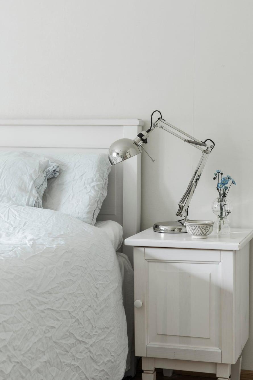 Makuuhuoneessa tavaran  määrä on minimoitu.  Siniset kukat maljakossa  luovat rauhallista  tunnelmaa.