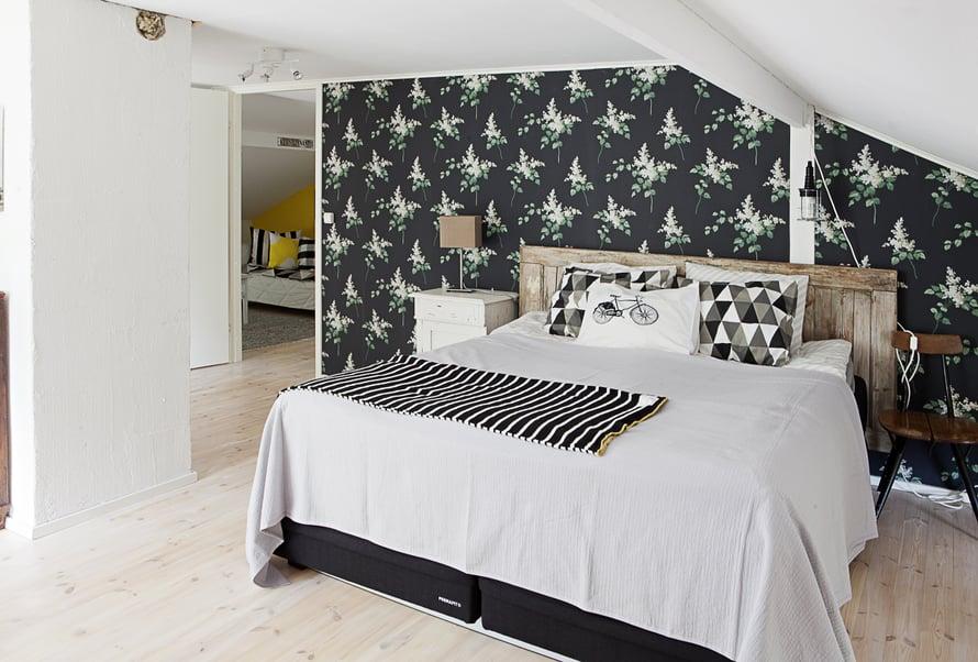 Makuuhuoneen tummapohjainen Sireeni-tapetti löytyi Boråstapeterin mallistosta. Vanha ovi sopii sängynpäädyksi.