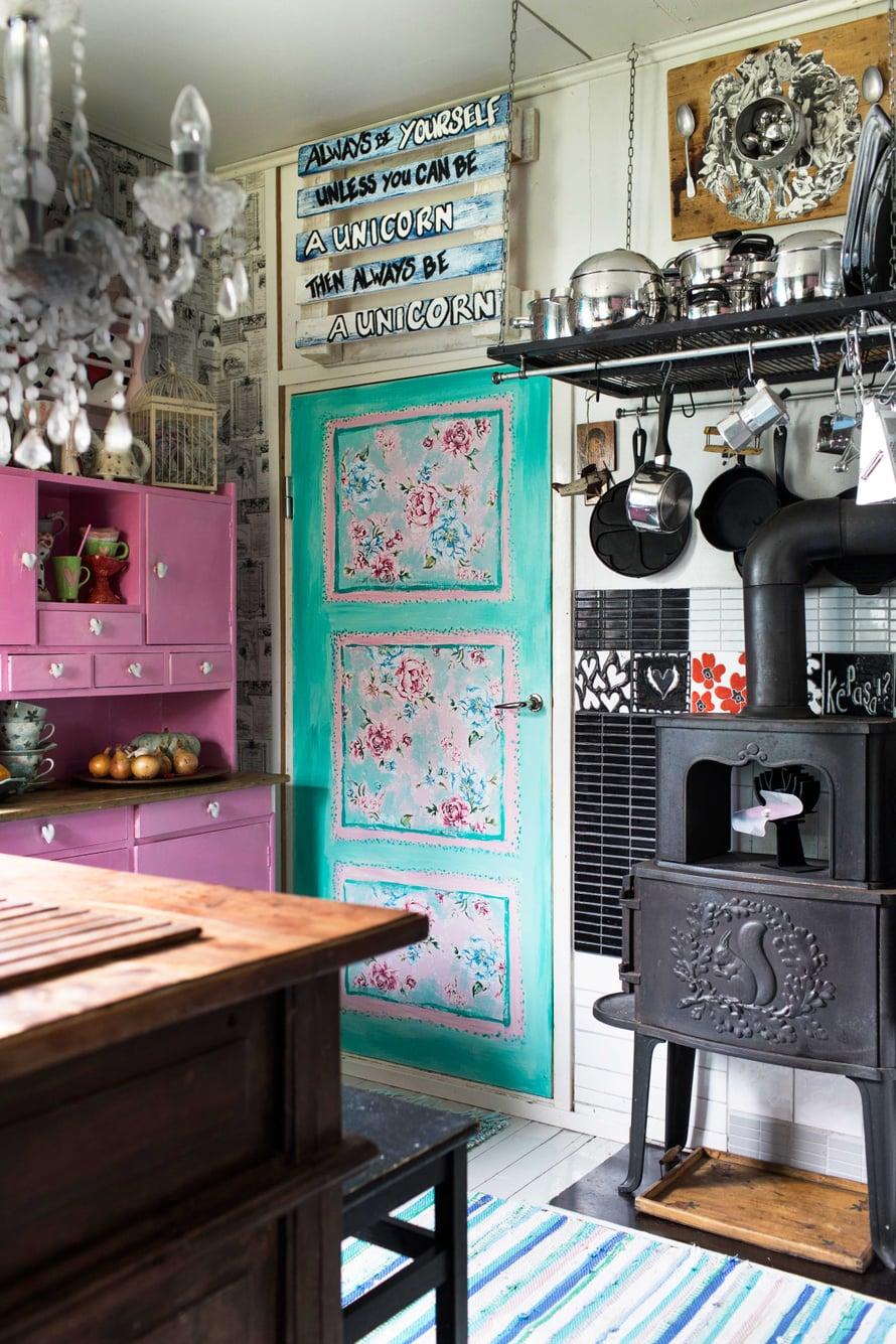 Kukat somistavat keittiöstä makuuhuoneeseen johtavaa ovea. Oven yläpuolella on tyttären lahja Marjolle. Kamiinan takana olevien seinälaattojen joukosta löytyy Marjon itse tekemiä kuviollisia laattoja.