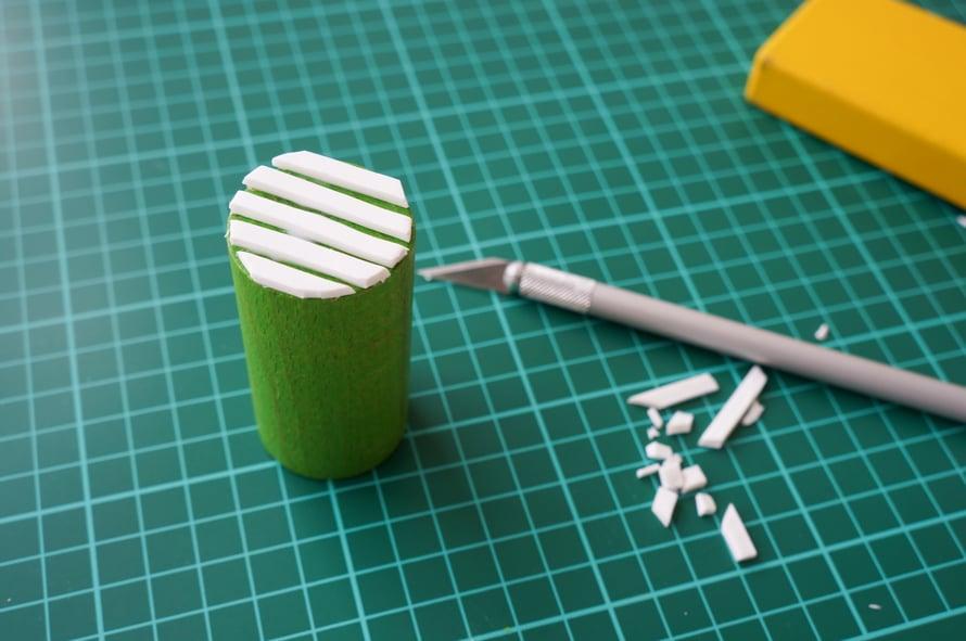 Ylimmän kuvan liinan raidallisten pallokuvioiden leimasin tehtiin puisesta lelupalikasta sekä Softis-levyn kapeista suikaleista. Reunat huoliteltiin terävällä veitsellä, jotta leimasinkuviosta tulee siisti.