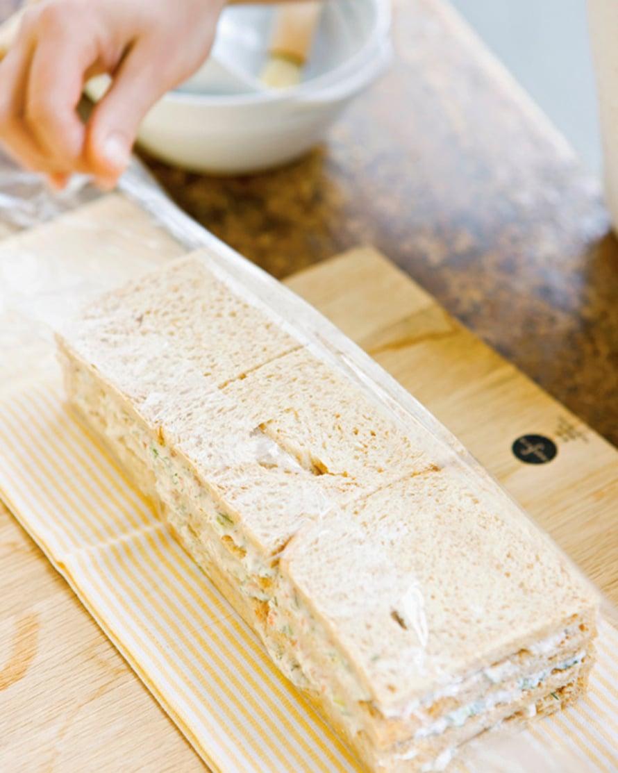 Nosta kelmun reunat voileipäkakun päälle tiiviisti. Kietaise vielä toinen kerros kelmua päälle tarvittaessa. Nosta pakettijääkaappiin  ja aseta tasainen paino päälle. Anna kakun vetäytyä ja kostua 12 tuntia eli puolisen vuorokautta.