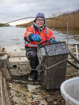 Liisa Vainio, 63, on kolmannen polven kalastaja ja asuu Taivassalossa. Työ koostuu suomukalan kalastuksesta verkoilla, kirjolohen kylmäsavustuksesta ja omien kalajalosteiden kuten maustettujen silakoiden, kalapihvien ja munkkitaikinaan leivottujen ahvenpötkösten valmistuksesta ja myynnistä.