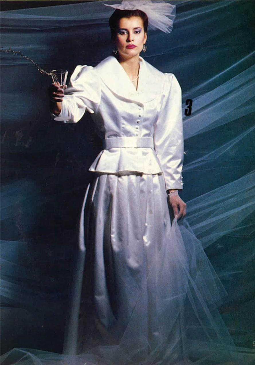 Rohkean morsiamen puku on vuodelta 1986. Jakkussa on mahtavat hihat ja helminauhalla koristeltu kauluksen ulkoreuna. Laskoshameen sivusaumaan on upotettu nenäliinatasku.