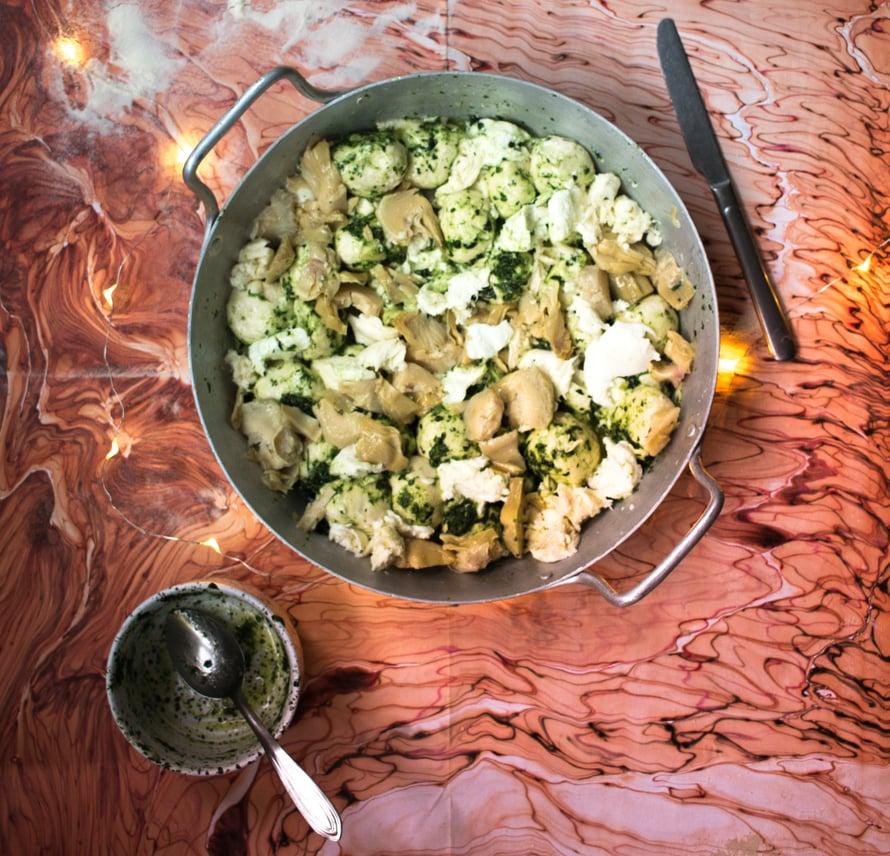 Tee yrttipesto ohjeen mukaan ja lisää se vuokaan, pyöritä taikinapallot öljyssä. Lisää vuokaan revitty mozzarella ja artisokan sydämet. Peitä kelmulla ja anna kohota jääkaapissa ainakin 12h.