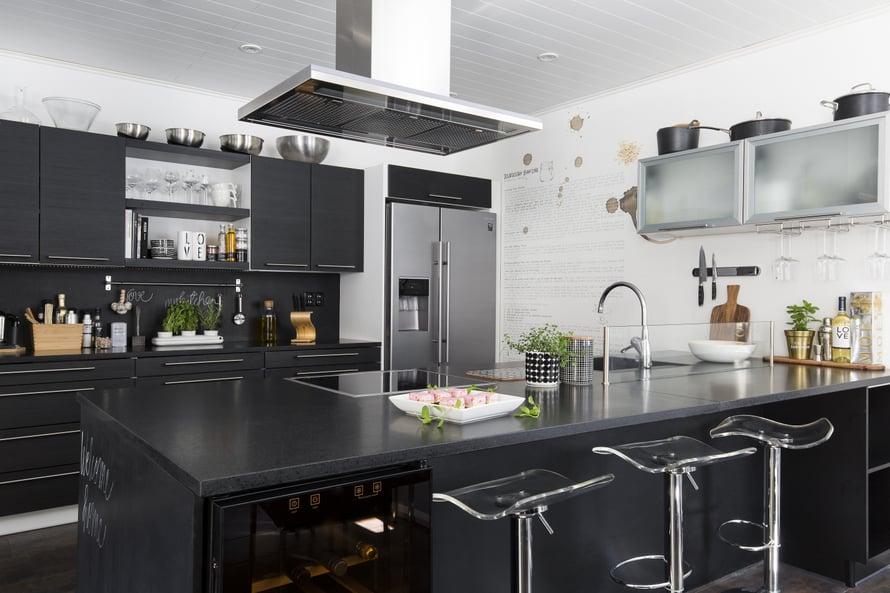 Puustellin keittiön kivitasot ovat helppohoitoiset. Saarekkeen ansiosta kokki voi puuhatessaan rupatella vieraiden kanssa.