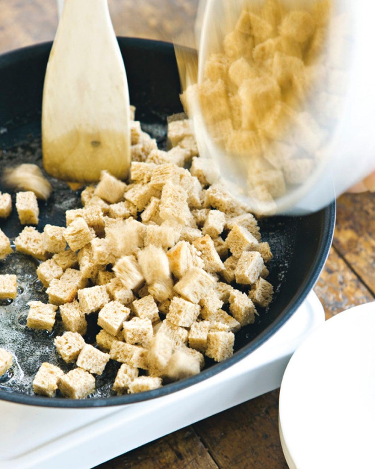 Leikkaa leipäviipaleet kuutioiksi. Kuumenna öljy ja voi paistinpannussa. Paahda kuutiot rapeiksi.