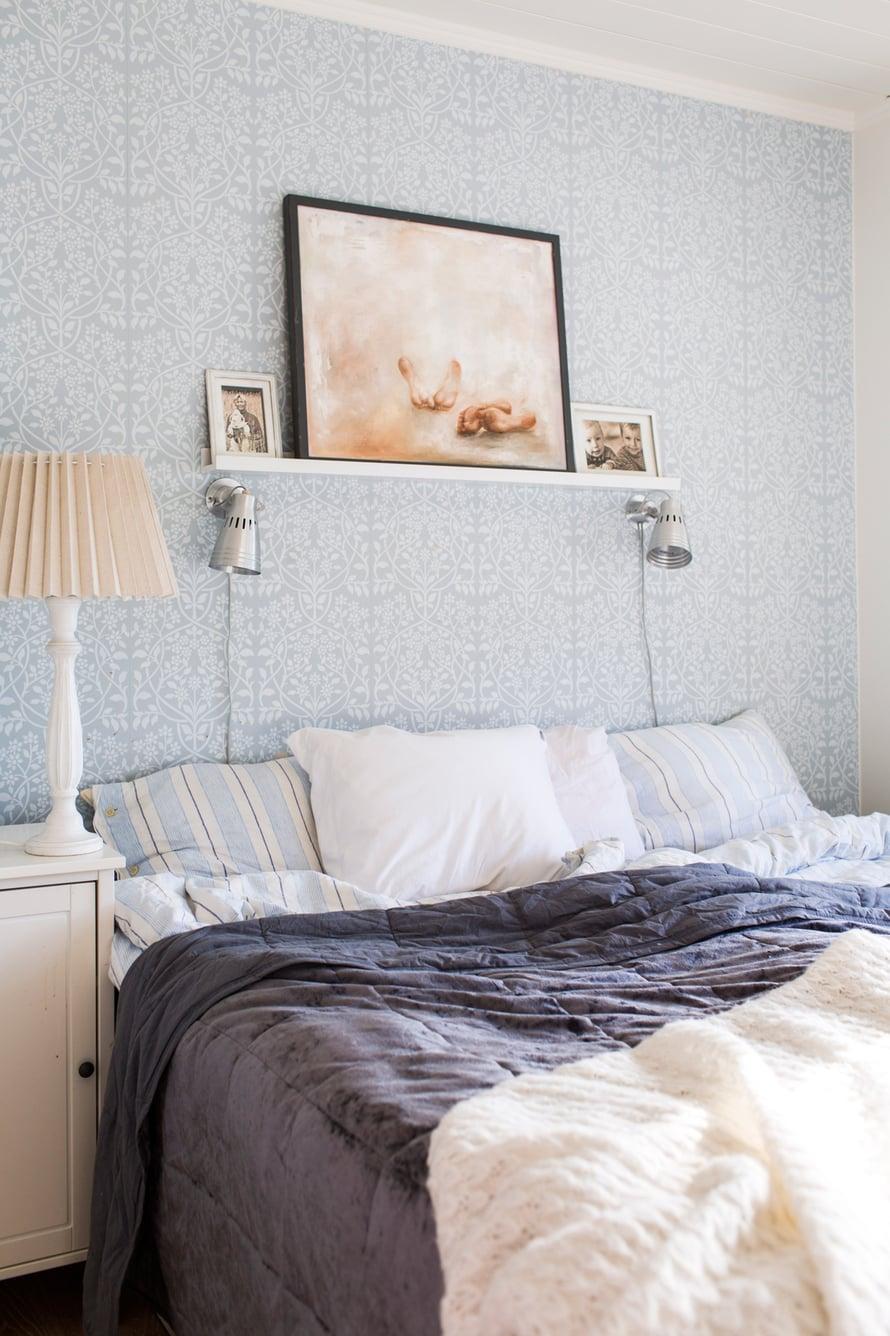 Makuuhuoneen värit valikoituivat Tapettitalon siniharmaan Lukko-tapetin mukaan. Hyllyllä on Johannan maalaus ja kuvia rakkaimmista.