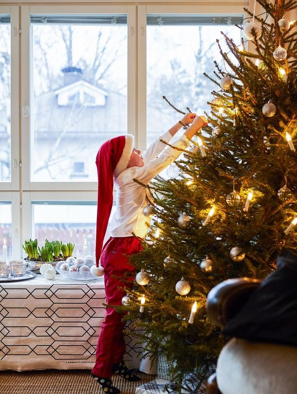 Erjon perheen kuusi on perinteisesti aito ja niin suuri kuin olkkariin sopii. Eemil auttaa äitiä koristelemaan kuusta hopeanvärisillä ja lasisilla palloilla.