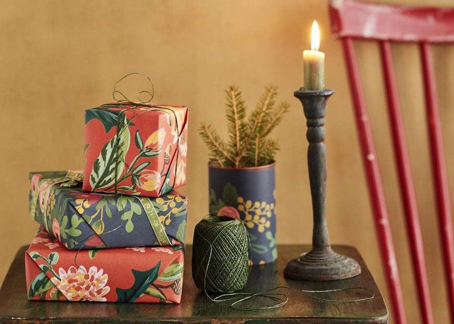 Tänä vuonna kuusen alta pilkottaa täyteläisiä värejä ja kukkakuoseja. Kuusiruukku syntyi päällystämällä peltipurkki lahjapaperilla. Rifle Paper -kukkapaperit Papershop, paperinaru Askarelli, peltipöytä Moko ja kynttilänjalka Mosa Interiors.