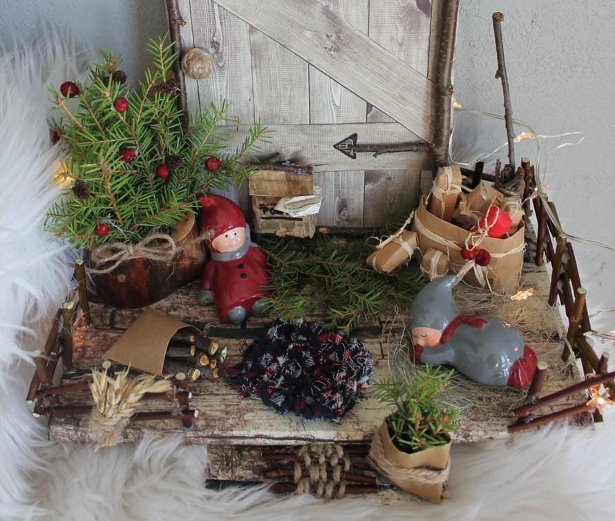 """""""Tontut ovat kovin väsyneitä näin joulun alla, joten tein puupalikasta, kuusen oksista ja pihlajanmarjoista toiselle tontulle nojaamispaikan. Toinen kovasti uurastanut tonttu pääsi meriheinän päälle lepäilemään."""""""