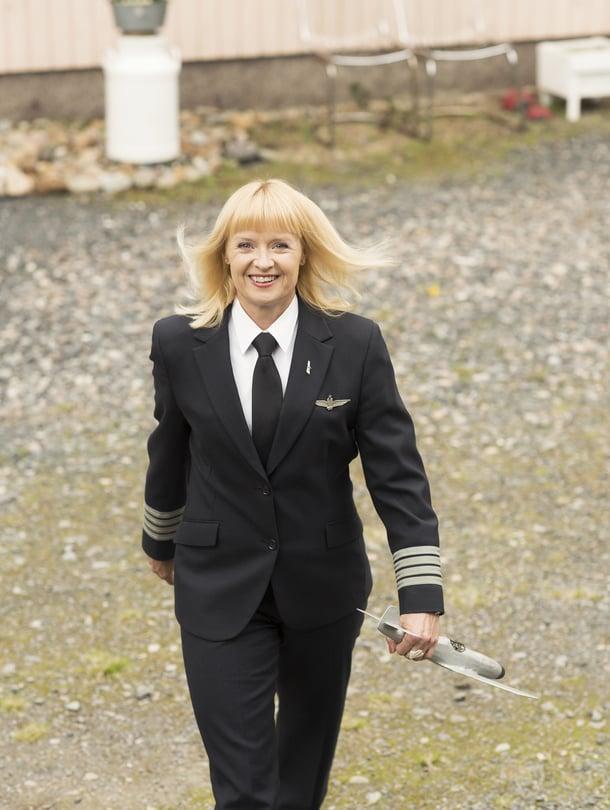 Maritsa Lindroos, 48, kotipihassa Laihialla tänä kesänä. Päällä lentokapteenin työasu, kädessä isän tekemä lentokone ajalta, jolloin tytöistä ei tullut lentäjiä.