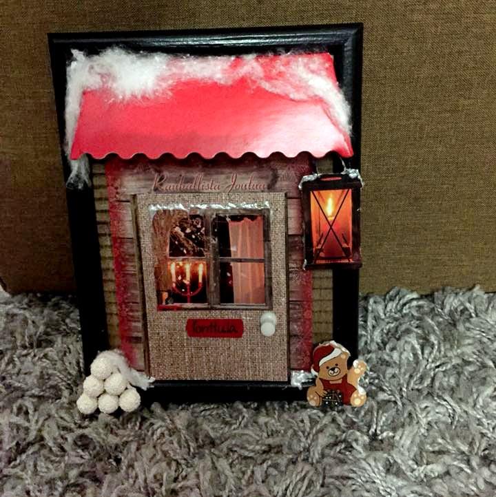 """""""Tein töihin tonttuoven:taulun kehys runkona, pahvista ja vanhoista joulukorteista leikkasin osia. Liimasin taakse pahvinpaloja, että se näyttäisi kolmiulotteiselta. Lyhty on tehty pienistä palloista, joista leikkasin rautalangat pois."""" Anne Koivisto"""