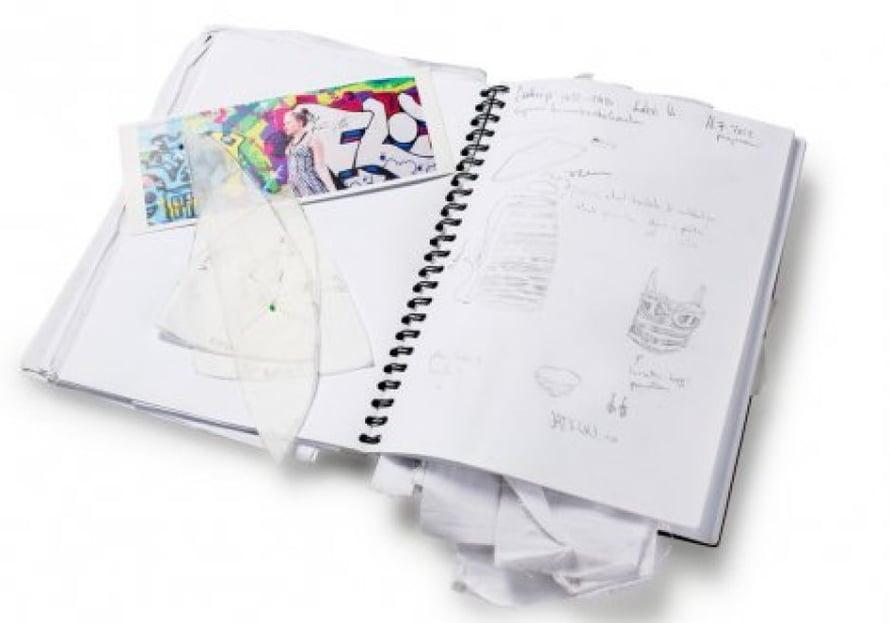 Luonnoskirjaan on koottu päättötyön suunnitteluprosessi, välistä löytyvät kaavat ja näyttelyn kutsukortti.