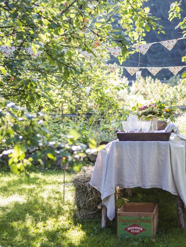 Jarkko rakensi pihapöydän peiliovista ja heinäseipäistä. Liina on pellavalakana, ja istuimeksi noudettiin heinäpaailit viereiseltä maatilalta.
