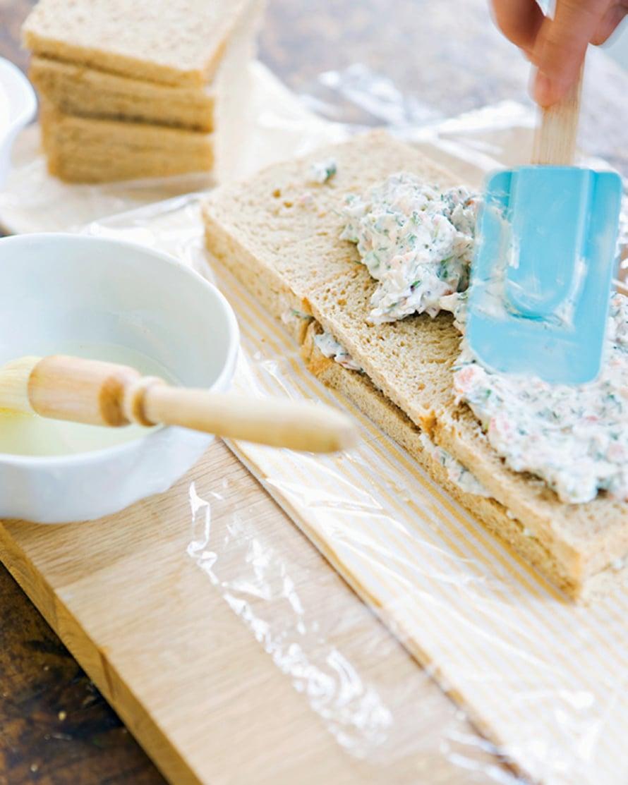 Levitä kostutettujen leipäviipaleiden päälle kolmasosa täytteestä. Nosta toinen kerros leipiä päälle, kostuta ja levitä täyte päälle. Toista vielä kolmannen kerran. Viimeiseksi tulee leipäkerros, joka vain kostutetaan