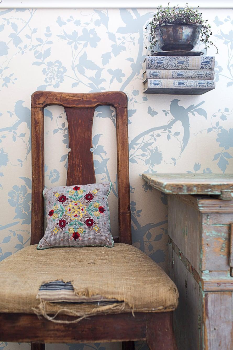 Tuolia on turha korjata, koska revennyt päällinen on vain sympaattinen. Kirjoista tehtyä hyllyä pitää seinällä alimman opuksen väliin liimattu kulmarauta.