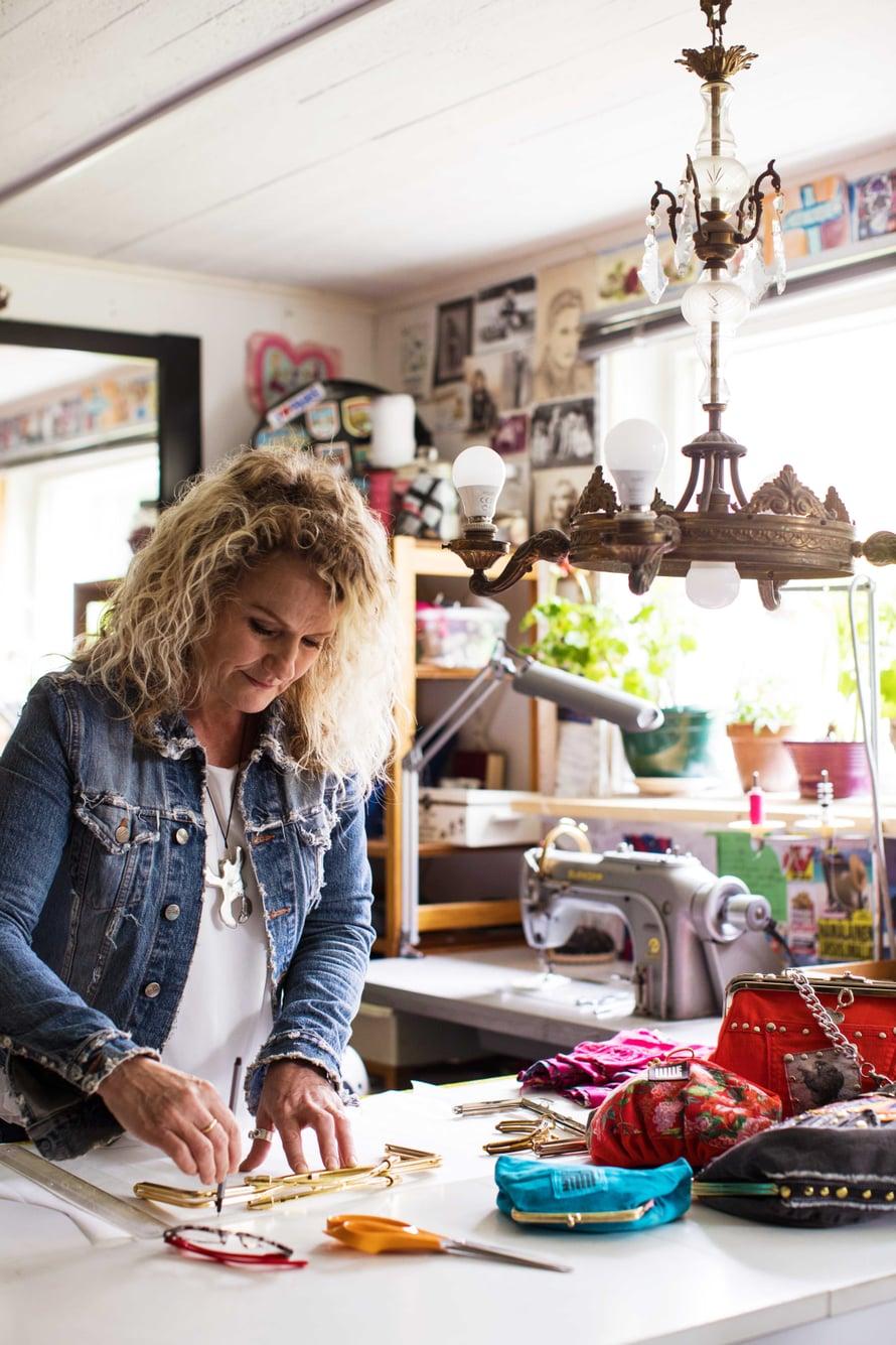 Työhuoneessaan kellarissa Marjo valmistaa laukkuja ja vaatteita kierrätysmateriaaleista.