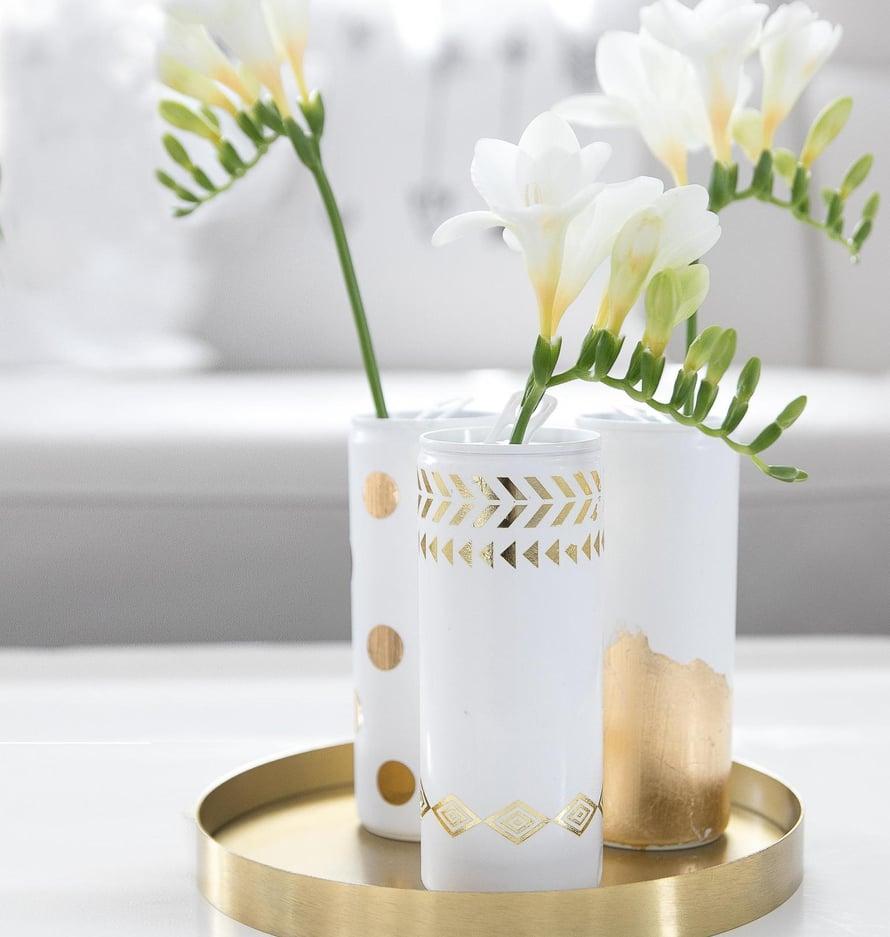 Kolmesta kapeasta energiajuomatölkistä saat siroimman maljakkoryhmän. Isompiin tölkkeihin mahtuu reilummin kukkia.